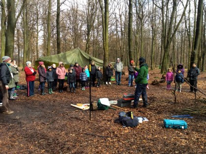 Primary School - full-day workshop in King's Wood with artist Tim Norris, March 2015.  Class, teachers and parents watch a demonstration by Tim of ways of working with different tools and forest materials to create shelters, constructions and standing forms.